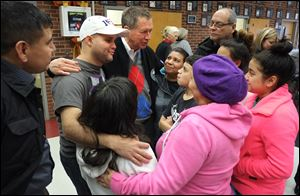 Ohio Gov. John Kasich, center, visits evacuees at Willard High School. Clockwise from far left are Adrian Lobo; Jovany Moya (white hat); Judith Moya; Leamsi Diaz, 13 (arms folded); Ismael Diaz (back right); Nashali Diaz, 18, (face hidden); Ana Santos; Lourdes Moya (beret), and Ambar Moya 13 (dark hair back to camera).