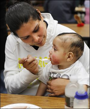 Melissa Rodriguez feeds her 9-month-old son, Abraham Aguilar, at a Thanksgiving dinner at Willard High School.