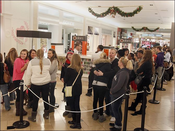 29n6shopping Customers wait to get into Pink, a clothing store in the Franklin Park mall, one of the retailers that opened on Thanksgiving evening for holiday shopping.