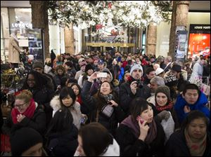 A shopper takes a selfie as crowds pour into the Macy's Herald Square flagship store Thursday in New York.