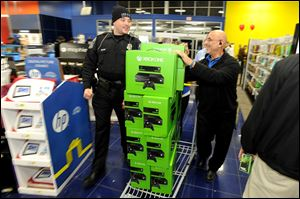 DeKalb police Officer Q.S. Starnes, left, helps Best Buy manager Sammy Abuata wheel in a pallet of Xbox One game sets for a door-buster sale just before midnight on Thanksgiving Day in Dunwoody, Ga. All of the store's 120 employees were on hand to ring up items after the electronics retailer opened on Thanksgiving this year.