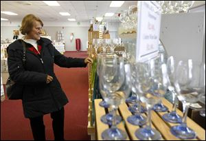 Ruth Frazier of Toledo looks at glassware at Libbey Glass' seasonal store in the Starlite Plaza in Sylvania. Libbey decided to open the site to capitalize on the number of shoppers in the western suburbs. The Monroe Street location will be open through Dec. 29.