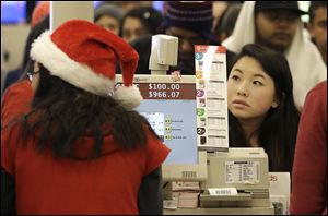 A shopper pays for her items at a cash register at a Target store in Colma, Calif., on Thanksgiving Day.