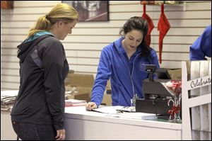 Joanna Joelson, left, of Toledo gets assistance from Libbey Glass employee Kirstin Stark at the Toledo glassmaker's outlet store in Sylvania.