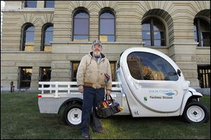 Gary Rogolsky, a maintenance worker at the Lucas County Courthouse, stands next to one of the electric-powered vehicles he uses to move between the county's 12 downtown Toledo buildings.