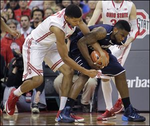 North Florida's Travis Wallace, right, battles Ohio State's Marc Loving for a loose ball in the first half. Loving scored seven points as the Buckeyes maintained their perfect record.