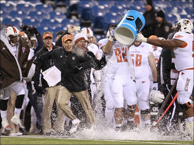 s7celebrate Bowling Green coach Dave Clawson gets a cold bath in celebration during the closing seconds of a victory over Buffalo at Ralph Wilson Stadium for the MAC East championship. The Falcons will play Northern Illinois on Friday for the confernce championship.
