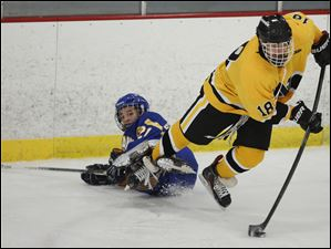Sylvania Northview's Caleb Rau (18) moves the puck against Findlay's Brandon Armstrong (21).