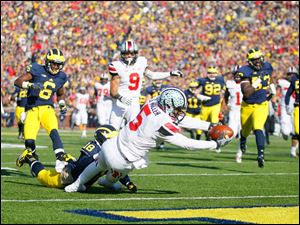 Ohio State quarterback Braxton Miller (5) scores a touchdown against University of Michigan's Blake Countess (18) during the first quarter.