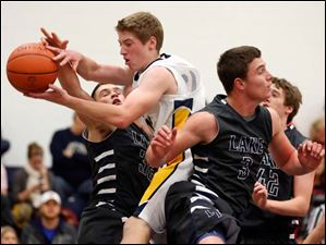 Toledo Christian's Kyle Kempton (11) goes to the net  against  Lake's Connor Bowen (32) and Jared Rettig (3).