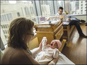 Zachary Bambacht spends time with his wife, Katie, and their 2-day-old daughter, Evie, in the postpartum department at Prentice Hospital in Chicago.