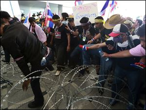 Anti-government protesters try to remove barbed wire during a rally in front of the Department of Special Investigation in Bangkok, Thailand.