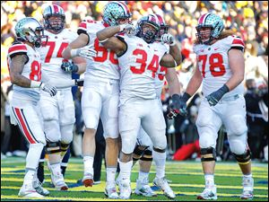 Ohio State running back Carlos Hyde (34) celebrates after scoring the final touchdown for the Buckeyes against Michigan during the fourth quarter. He ran for a game-high 226 yards.
