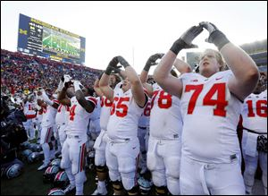Ohio State University player Jack Mewhort (74) and teammates celebrate their 42-41 win over the University of Michigan in Ann Arbor, Saturday.
