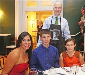 Joe Nugent, sports anchor/reporter at WTVG-TV, Channel 13, standing, waits on Margarita Beale, seated at left, and her children Timothy, 14, and Caroline, 11, at the Family and Child Abuse Prevention Center's Celebrity Wait NIght.