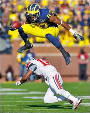 Michigan's Devin Funchess leaps over Ohio State's Doran Grant in the second quarter. Funchess scored one of four UM passing TDs.