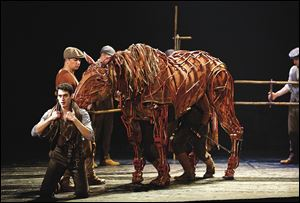 Michael Wyatt Cox as Albert, foreground, with the horse Joey, in 'War Horse.' Human puppeteers control the movements of Joey and the other horses in the show.