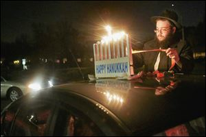Other cars arrive as Tzemach Shemtov fastens a menorah to the rooftop before the beginning of the third annual Chanukah Menorah Car Parade near Chabad House in Toledo.