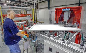 Kevin Morris uses a machine to crimp the corners of a 250 watt solar panel frame at Isofoton's $31 million factory in Napoleon. In total, Isofoton North America garnered $8.4 million in local and state incentives.