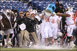 Bowling Green coach, Dave Clawson, gets the water bucket dumped on him in the closing seconds of a 24-7 victory over the University of Buffalo at Ralph Wilson Stadium for the MAC East championship, on Friday.