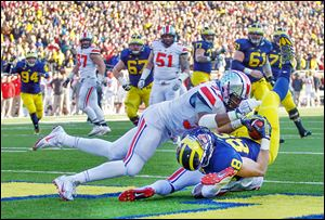 Michigan tight end Jake Butt lands in the end zone for a touchdown as Ohio State players Joshua Perry, left, and Corey Brown defend during the fourth quarter. Butt had five catches for 85 yards.