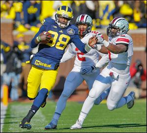 Ohio State linebacker Ryan Shazier (2) and defensive lineman Noah Spence chase Michigan quarterback Devin Gardner. Gardner threw for 451 yards and four touchdowns against the Buckeyes.