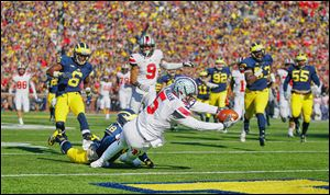 Ohio State quarterback Braxton Miller scores a touchdown as Michigan defensive back Blake Countess tries to stop him.