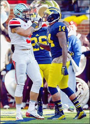 Ohio State receiver Devin Smith quiets the crowd after scoring a touchdown in front of Michigan's player Josh Furman.