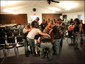 A group places their hands on Tanya Zam, who recently had knee surgery, and pray over her during a service.