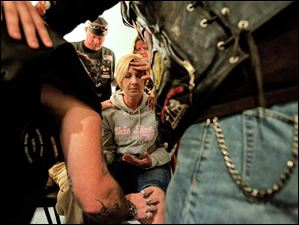 A group of bikers place their hands on Tanya Zam, who recently had knee surgery, and pray over her during a service on Aug. 14 at Heaven's Highway Biker Church.