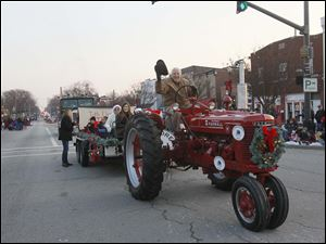 A Mccormick Farmall tractor pulls the Toth Elementary School Artists of the Month in the parade.
