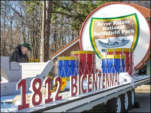 Bill Saul secures chicken wire that will brace artificial snow  on the River Raisin National Battlefield Park's float for the festival. It has a new trailer, donated by American Manufacturing Operations of Toledo.