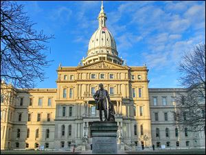 Gov. Austin Blair, the war governor (1861- 1864), is silhouetted against the Michigan state Capitol in Lansing, Mich.