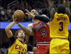 Chicago Bulls' Carlos Boozer (5) shoots against Cleveland Cavaliers' Anderson Varejao, left, of Brazil, and Dion Waiters (3) in the first quarter of an NBA basketball game Saturday.