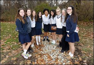 St. Ursula Academy's STEM Club includes, from left, Caroline Lewandowski, Beatrice Thaman, Alyssa Brown, Jasmine Arndt, Charese Foster, Neera Martin, Mattison Gibson, adviser Jackie Kane, and Maddie Krell, at their rain garden at the school.