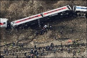 Emergency rescue personnel work the scene of a Metro-North passenger train derailment in the Bronx borough of New York today. Four people were killed and more than 60 were injured.