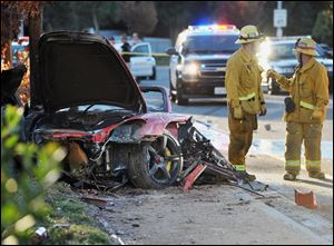 Sheriff's deputies work near the wreckage of a Porsche that crashed into a light pole on Hercules Street near Kelly Johnson Parkway in Valencia, Calif., on Saturday.
