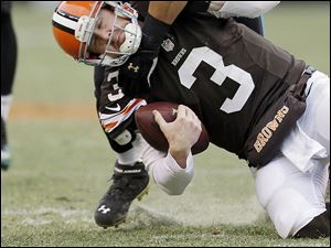 Brandon Weeden is tackled by Jacksonville's Jason Babin during the third quarter on Sunday. Weeden suffered a concussion at some point in the game.