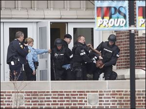 Toledo police remove an unidentified student from Scott High School after a standoff today.