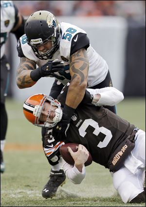 Cleveland Browns quarterback Brandon Weeden (3) is tackled by Jacksonville Jaguars defensive end Jason Babin (58) during the third quarter Sunday.