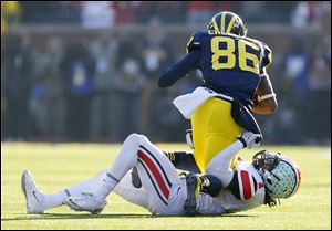 Ohio State's Bradley Roby wraps up Michigan's Jehu Chesson during the third quarter on Saturday in Ann Arbor. The Buckeyes' defense surrendered 603 yards, including 451 passing yards.