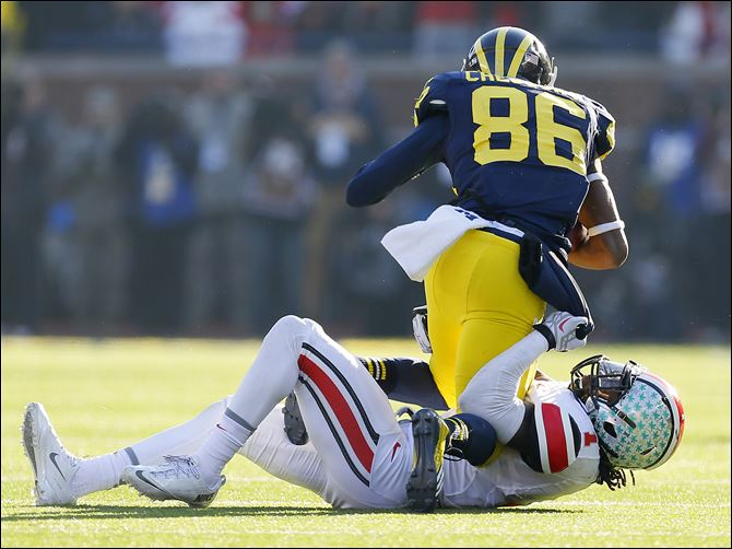 03s3roby Ohio State's Bradley Roby wraps up Michigan's Jehu Chesson during the third quarter on Saturday in Ann Arbor. The Buckeyes' defense surrendered 603 yards, including 451 passing yards.