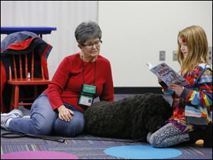 Clara Burkin, 8, Perrysburg, reads a story to Sue Davis and her golden doodle