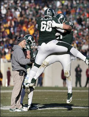 Tyler Hoover, right, celebrates his fumble recovery with Michigan State teammate Micajah Reynolds during Saturday's win.