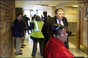 Building managers, government officials and repairmen stand in the lobby of Alpha Towers near downtown Toledo.