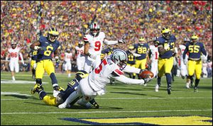 OSU quarterback Braxton Miller runs for one of his three touchdowns against Michigan on Saturday in Ann Arbor. Miller repeated as Big Ten offensive player of the year on Tuesday night.