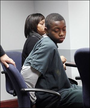 Louis Stroude, 14, and his mother, Lonyel Cole, await his hearing in Juvenile Court. Police said Louis had a pellet gun and a knife in his bookbag at Scott High School. the freshman was charged with making terrorist threats and illegal conveyance of a dangerous weapon onto school property.