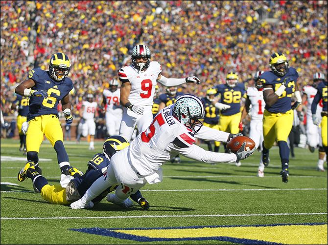 s4brazton OSU quarterback Braxton Miller runs for one of his three touchdowns against Michigan on Saturday in Ann Arbor. Miller repeated as Big Ten offensive player of the year on Tuesday night.