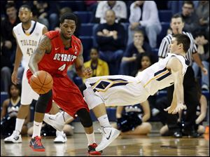 Toledo guard Jordan Lauf (25) defends against Detroit forward Patrick Onwenu (4).
