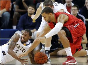 Toledo guard Rian Pearson (5) steals the ball from Detroit forward Jermaine Lippert (21).